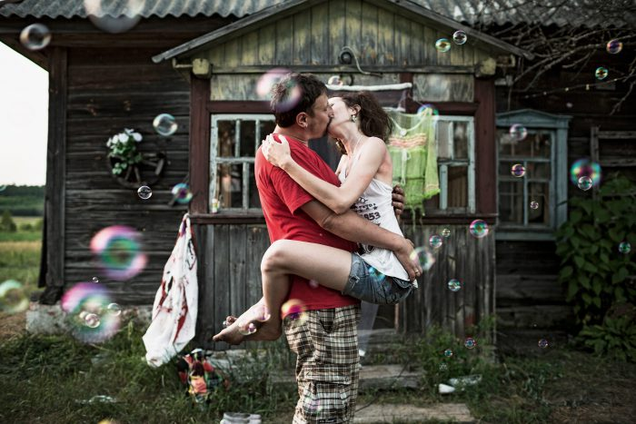 Zhenya (Evgeny) and Yulia kiss in front of their datcha during their wedding celebration with their friends.